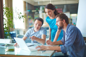 Group of three successful business partners in casual discussing data in laptop at meeting in office